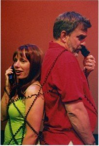 Man and Woman Both Holding Phone to Their Ears while Tangled Together in the Curly Phone Cords