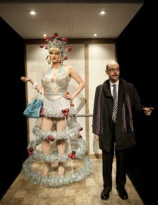 Tall White Drag Queen In Silver and Red Christmas Tree Drag and Nerdy Looking Bald White Man With Glasses and Business Jacked Standing Together in Stalled Elevator