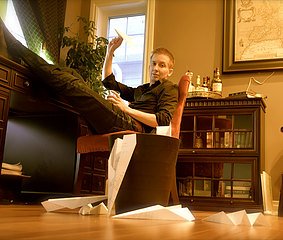 White Man With Short Hair Sitting At Desk With Feet on Table Behind Trash bin Surrounded By Paper Planes