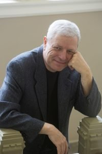 Older White Man with White Hair Leaning on Railing and Looking at Camera