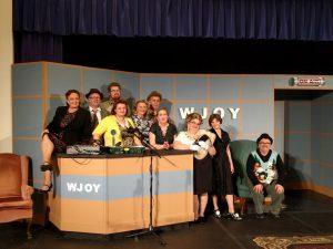 Dozen Cast Members Posing on Set That Looks Like A WJOY Radio Studio