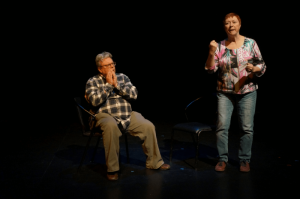 Older White man and Older White Woman On Stage, Woman Standing Man Sitting