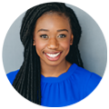 Black Woman Wearing Blue Smiles and Looks Into The Camera