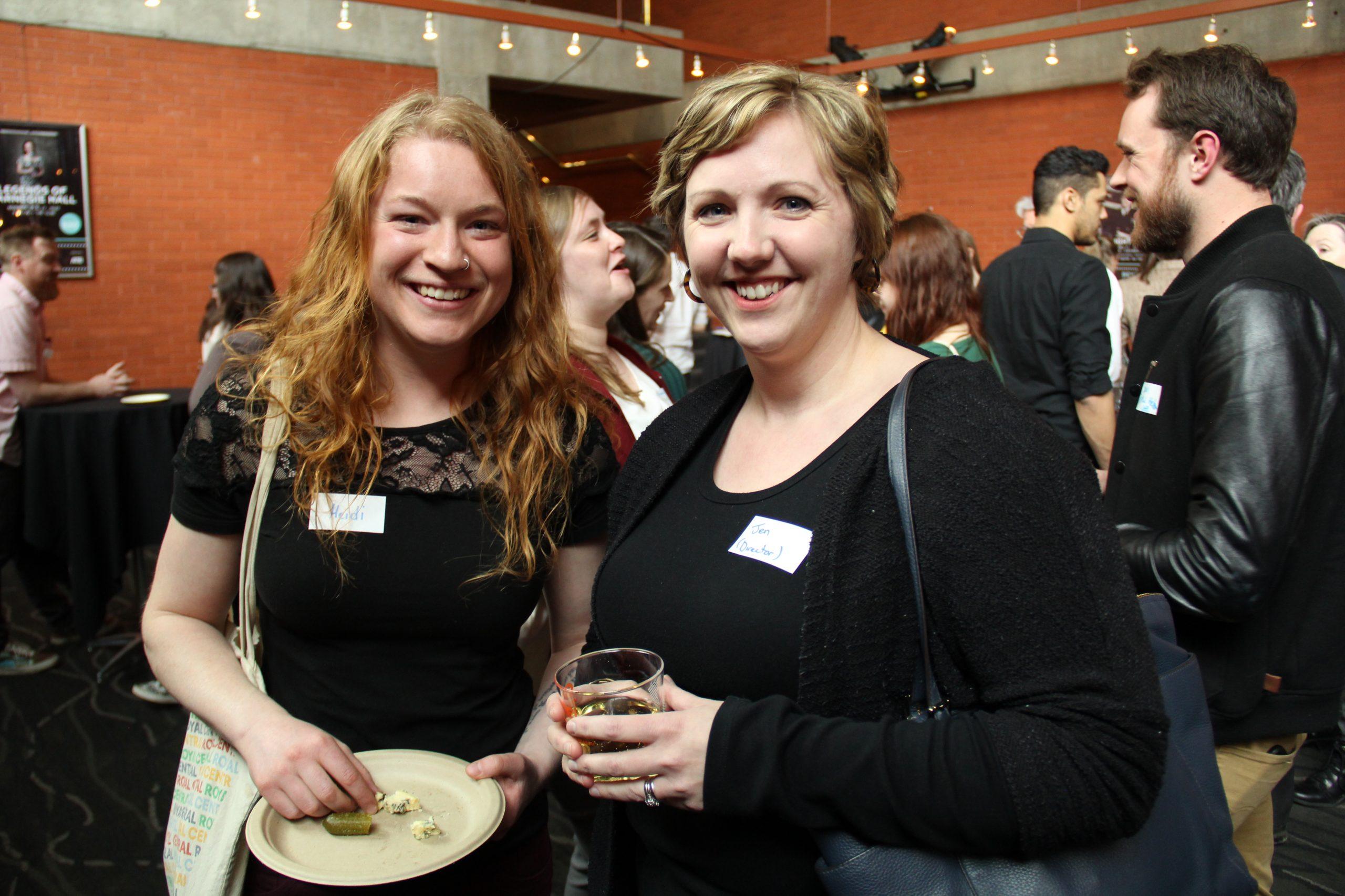 two white women wearing black at Emerge 2016 meet and greet, smiling while enjoying food and drink