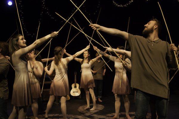 Photo of actors holding up sticks. Dark background.