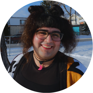 Smiling Woman With Black Glasses and Cool Dark Hair in Two Buns With Chunks Framing Face And Neon Pink Crescent Moon Necklace Standing in Snowy Park