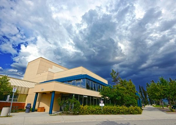 The Yukon Arts Centre, a Beige and Blue Building Under a Summer Sky
