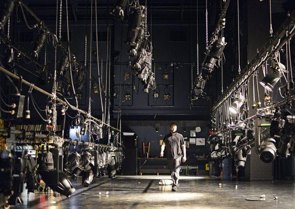 Man In Black Walking Backstage Among Theatre Lights Hung on Horizontal Poles