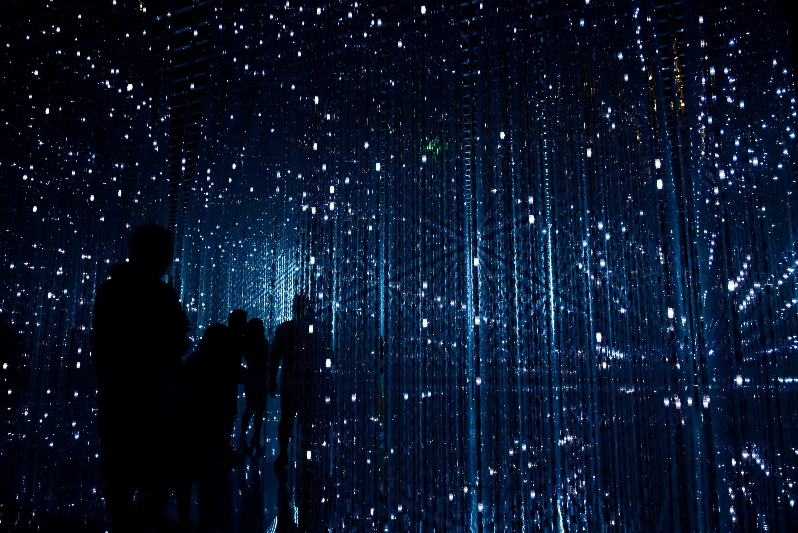Futuristic Image of Silhouetted People In Dark Room With Blue Lines and White Sparks Of Light